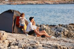 Φιλική ειλικρινής οικογένεια που στηρίζεται στη δύσκολη παραλία κοντά στη σκηνή Στοκ εικόνα με δικαίωμα ελεύθερης χρήσης