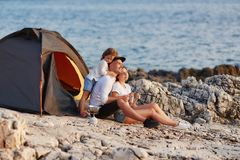 Φιλική ειλικρινής οικογένεια που στηρίζεται στη δύσκολη παραλία κοντά στη σκηνή Στοκ φωτογραφίες με δικαίωμα ελεύθερης χρήσης