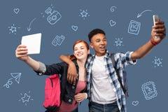 Φιλικοί έφηβοι που κρατούν τις σύγχρονες συσκευές και που παίρνουν selfies στοκ εικόνες με δικαίωμα ελεύθερης χρήσης