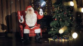 Φιλικός Άγιος Βασίλης με τις χειρονομίες σπινθηρισμάτων, που χορεύουν κοντά στη νέα διακοσμημένη έτος εστία απόθεμα βίντεο