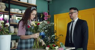 Φιλικός ανθοκόμος που τακτοποιεί τα λουλούδια και που μιλά στον πελάτη επιχειρηματιών στο κατάστημα