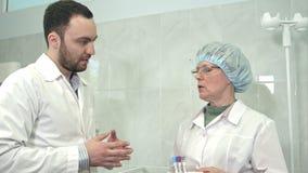 Φιλικός αρσενικός γιατρός που μιλά στα δείγματα αίματος εκμετάλλευσης νοσοκόμων απόθεμα βίντεο
