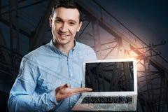 Φιλικός επιχειρηματίας που δείχνει προς την οθόνη του lap-top Στοκ Φωτογραφίες