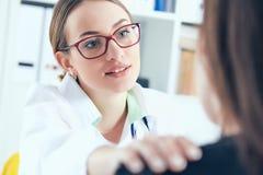 Φιλικός θηλυκός γιατρός στα γυαλιά σχετικά με τον υπομονετικό ώμο Ενθάρρυνση, ενσυναίσθημα, ενθαρρυντικός και υποστήριξη μετά από Στοκ Εικόνες