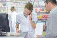 Φιλικός θηλυκός συμβουλευτικός ασθενής φαρμακοποιών μέσω του τηλεφώνου στο φαρμακείο στοκ εικόνες