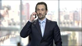 Φιλικός καυκάσιος επιχειρηματίας που μιλά στο τηλέφωνο κυττάρων απόθεμα βίντεο