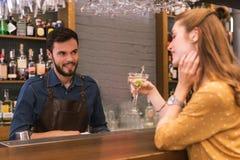 Φιλικός μπάρμαν που εξετάζει τον πίνοντας επισκέπτη και το χαμόγελο στοκ φωτογραφίες