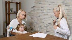 Φιλικός παιδίατρος που εξοικειώνεται με τη νέες μητέρα και την αρκετά λίγη κόρη Έννοια οικογενειακών κλινικών 4K φιλμ μικρού μήκους