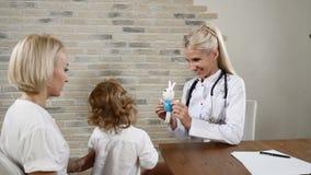 Φιλικός παιδίατρος που εξοικειώνεται με τη νέες μητέρα και την αρκετά λίγη κόρη Έννοια οικογενειακών κλινικών 4K απόθεμα βίντεο