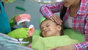 Φιλικός παιδιατρικός οδοντίατρος που εξηγεί στο παιδί πώς να βουρτσίσει τα δόντια κατάλληλα απόθεμα βίντεο