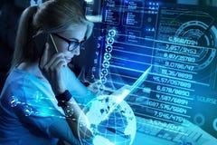 Φιλικός προγραμματιστής που μιλά στο τηλέφωνο εξετάζοντας τη σύγχρονη συσκευή της στοκ εικόνες