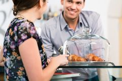 Φιλικός σερβιτόρος που προσφέρει στο νέο θηλυκό πελάτη φρέσκο γαλλικό γ Στοκ φωτογραφίες με δικαίωμα ελεύθερης χρήσης