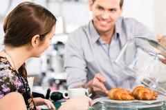 Φιλικός σερβιτόρος που προσφέρει στο νέο θηλυκό πελάτη φρέσκο γαλλικό γ Στοκ εικόνες με δικαίωμα ελεύθερης χρήσης