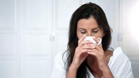 Φιλικός σκεπτικός τσάι ή καφές κατανάλωσης γυναικών πορτρέτου που απολαμβάνει το πρωί στο σπίτι ή το εσωτερικό ξενοδοχείων απόθεμα βίντεο