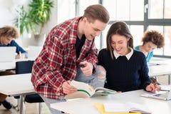Φιλικός σπουδαστής που βοηθά το συμμαθητή του με την εξήγηση και την παρουσίαση της απάντησης Στοκ Φωτογραφίες