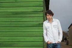 Φιλικός τύπος που κλίνει ενάντια σε έναν ξύλινο τοίχο Στοκ Εικόνες