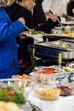 Φιλοξενούμενοι που αρπάζουν τα τρόφιμα σε έναν μπουφέ Στοκ εικόνες με δικαίωμα ελεύθερης χρήσης