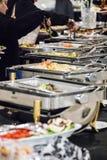 Φιλοξενούμενοι σε έναν μπουφέ τροφίμων Στοκ Φωτογραφίες