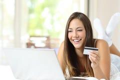 Φιλοξενούμενος που πληρώνει on-line με την πιστωτική κάρτα σε ένα κρεβάτι στοκ φωτογραφία