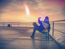 φιλτραρισμένος Ο τουρίστας κάθεται στον πάγκο χάλυβα στον τυφλοπόντικα και παίρνει το σπάσιμο στοκ φωτογραφίες με δικαίωμα ελεύθερης χρήσης