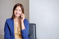 Φιλόδοξη επιχειρηματίας που μιλά τηλεφωνικώς στο σύγχρονο εργασιακό χώρο γραφείων στοκ εικόνες
