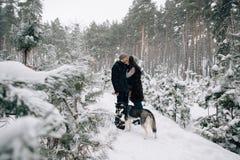 Φιλώντας ζεύγος που περπατά με το σκυλί στο χιονώδες δάσος στοκ φωτογραφία με δικαίωμα ελεύθερης χρήσης