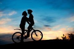 Φιλώντας το ρομαντικό ζεύγος ερωτευμένο στο ηλιοβασίλεμα στοκ εικόνα