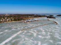 Φινλανδία Έσποο, μαρίνα Nuottanimi μια ημέρα άνοιξη με το νερό ακόμα στον πάγο και τις βάρκες που αποθηκεύονται στο έδαφος Στοκ Εικόνα