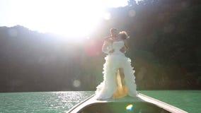 φιλί νυφών και νεόνυμφων που στέκεται στη βάρκα longtail στο backlight απόθεμα βίντεο