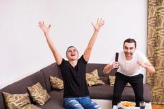 Φιλαράκοι που προσέχουν τον αγώνα ποδοσφαίρου στη TV στο σπίτι με τις κραυγές νίκης Στοκ φωτογραφία με δικαίωμα ελεύθερης χρήσης