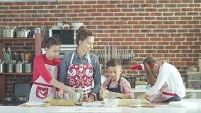 Φιλική και ευτυχής οικογένεια που προετοιμάζει τα μπισκότα στην κουζίνα απόθεμα βίντεο