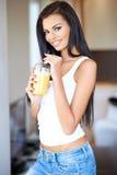 Φιλική όμορφη γυναίκα που πίνει το χυμό από πορτοκάλι Στοκ Εικόνες
