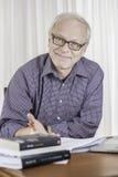 Φιλικός ανώτερος επιχειρηματίας που εργάζεται στο γραφείο του Στοκ Εικόνες