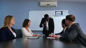 Φιλικός βέβαιος αφρικανικός επιχειρηματίας σε μια διοικητική συνεδρίαση με μια ομάδα πολυφυλετικών συναδέλφων απόθεμα βίντεο