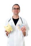 Φιλικός γιατρός με τα χρήματα και piggybank Στοκ Φωτογραφία
