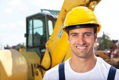 Φιλικός εργάτης οικοδομών μπροστά από τον εκσκαφέα του Στοκ φωτογραφία με δικαίωμα ελεύθερης χρήσης