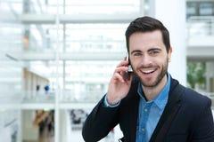 Φιλικός νεαρός άνδρας με το κινητό τηλέφωνο Στοκ Φωτογραφίες