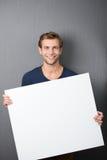 Φιλικός όμορφος νεαρός άνδρας με ένα κενό σημάδι Στοκ εικόνα με δικαίωμα ελεύθερης χρήσης