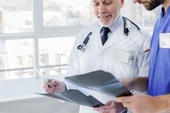 Φιλικός ώριμος ιατρός παθολόγος που συνεργάζεται με το βοηθό Στοκ Εικόνες