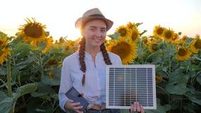 Φιλικό προς το περιβάλλον, θηλυκό χαμόγελο στην αναδρομικά φωτισμένη συντήρηση ακολουθώντας ήλιο μπαταριών χεριών στον κινητό και φιλμ μικρού μήκους