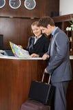 Φιλοξενούμενος που εξετάζει το χάρτη πόλεων με το ρεσεψιονίστ ξενοδοχείων στοκ φωτογραφία με δικαίωμα ελεύθερης χρήσης