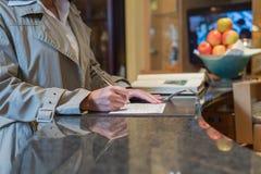 Φιλοξενούμενος που συμπληρώνει την αίτηση εγγραφής στοκ εικόνες με δικαίωμα ελεύθερης χρήσης