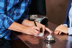 Φιλοξενούμενος στην υποδοχή ξενοδοχείων που πληρώνει με τον έλεγχο στοκ φωτογραφία