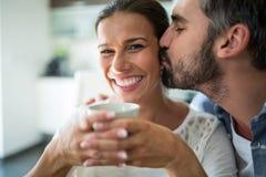 Φιλώντας γυναίκα ανδρών στα μάγουλα ενώ έχοντας τον καφέ στοκ φωτογραφία