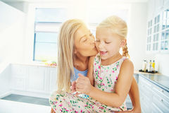 Φιλώντας κόρη μητέρων στη φωτεινή κουζίνα Στοκ φωτογραφίες με δικαίωμα ελεύθερης χρήσης