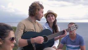 Φλερτάροντας, νέα εύθυμα μάτια φλερτ κοριτσιών ερωτευμένα στην κιθάρα παιχνιδιού τύπων κατά τη διάρκεια του κόμματος φίλων στη φύ απόθεμα βίντεο