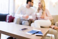 φλιτζάνια του καφέ εκμετάλλευσης ζευγών με το smartphone, τα διαβατήρια και τα εισιτήρια Στοκ εικόνες με δικαίωμα ελεύθερης χρήσης