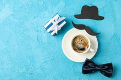 Φλιτζάνι του καφέ, δεσμός τόξων, κιβώτιο δώρων, διακοσμητικά mustache και καπέλο στο μπλε υπόβαθρο, διάστημα για το κείμενο στοκ φωτογραφίες με δικαίωμα ελεύθερης χρήσης