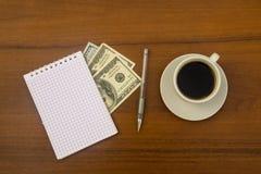 Φλιτζάνι του καφέ, δολάρια, σημειωματάριο και μάνδρα στο ξύλινο γραφείο Στοκ φωτογραφία με δικαίωμα ελεύθερης χρήσης