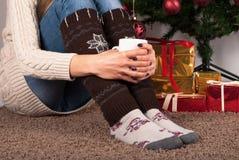 Φλιτζάνι του καφέ και συνεδρίαση εκμετάλλευσης νέων κοριτσιών στο πάτωμα ταπήτων, το χριστουγεννιάτικο δέντρο και το παρόν κιβώτι Στοκ φωτογραφίες με δικαίωμα ελεύθερης χρήσης